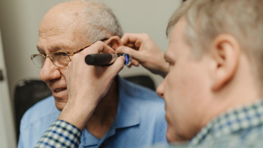 Andrew Sharpe performing a hearing test on a patient