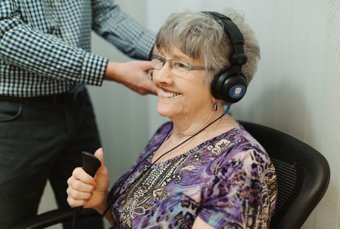 Photo of a lady at the Sharpe Hearing Clinic smiling having her ears tested